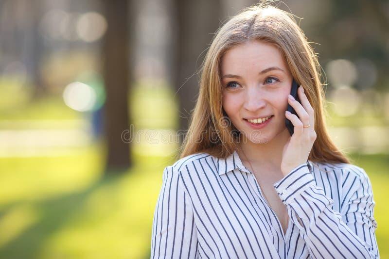 Junge nette lächelnde Frau, die draußen am intelligenten Telefon spricht Conver lizenzfreie stockbilder
