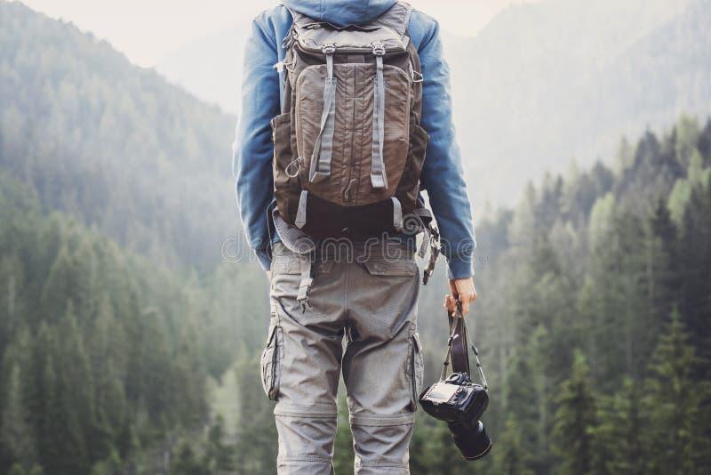 Junge nette Mannphotograph-Holdingdigitalkamera in Berge Fotografie, Reise und aktiver Lebensstil c lizenzfreies stockbild
