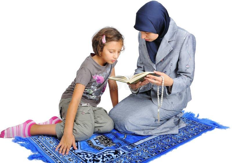 Junge nette moslemische Frau, die ihre Tochter unterrichtet lizenzfreie stockfotos