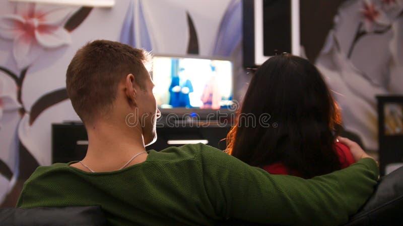 Junge nette Paare, die auf einer Couch zusammen fernsieht sitzen Junger Mann umarmt seine Freundin lizenzfreies stockbild