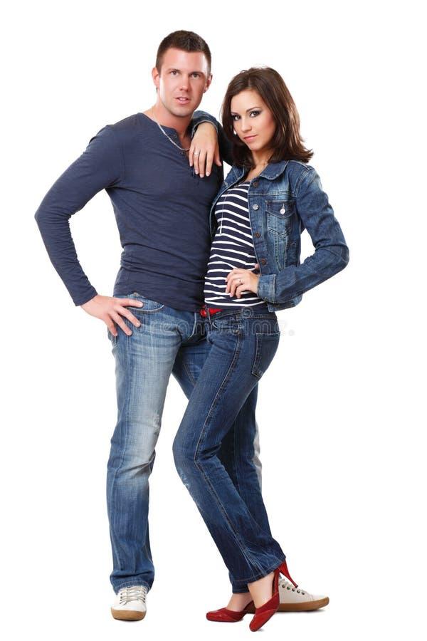 Junge nette Paare, die auf weißem Hintergrund aufwerfen stockfotografie
