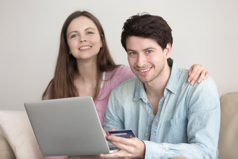 Junge nette Paare, die online über Laptop mit Kredit Ca kaufen stockfoto