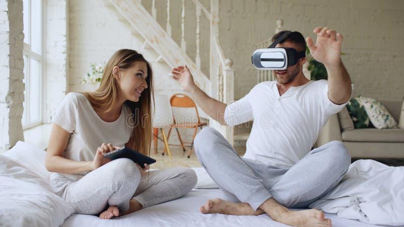 Junge nette Paare mit dem Tablet-Computer und Kopfhörer der virtuellen Realität, die 360 VR-Videospiel beim Sitzen im Bett an spi stockfotos