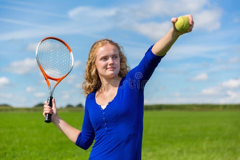 Junge niederländische Frau, die draußen Tennisschläger und -ball hält stockfotos