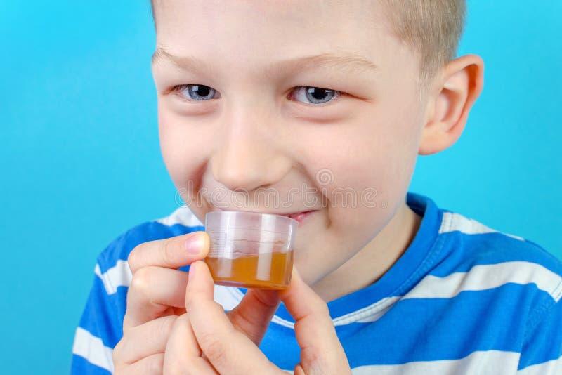 Junge nimmt multi Vitaminsirup auf blauem Hintergrund lizenzfreies stockfoto