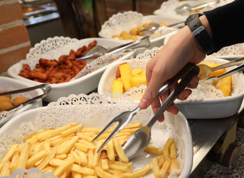 Junge nimmt Pommes-Frites mit einem Paar Zangen im Schule-cante stockbilder