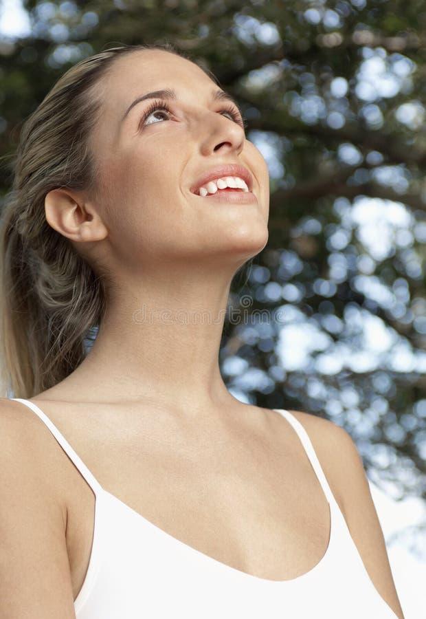 Junge oben schauende und lächelnde Frau stockfoto