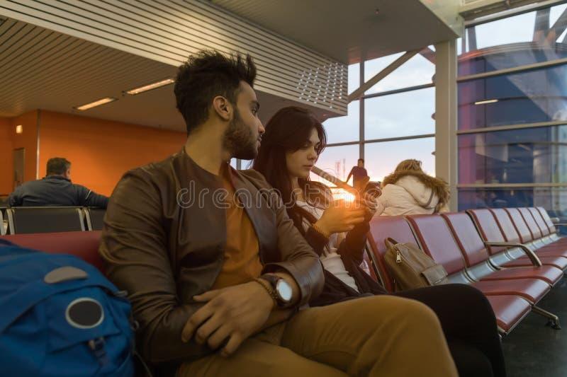 Junge Paar-Sit In Airport Lounge Waiting-Abfahrt-hispanisches Mann-und Frauen-Gebrauchs-Zell-Smart-Telefon stockfoto
