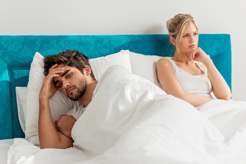 Junge Paare auf dem Bett; Probleme im Schlafzimmer lizenzfreie stockfotografie