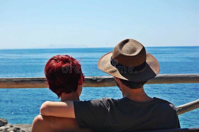 Junge Paare auf dem Seeufer lizenzfreie stockbilder