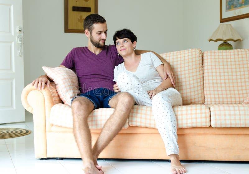 Junge Paare auf dem Sofa Mann und Frau, die beim Sitzen auf der Couch umfassen lizenzfreie stockfotos
