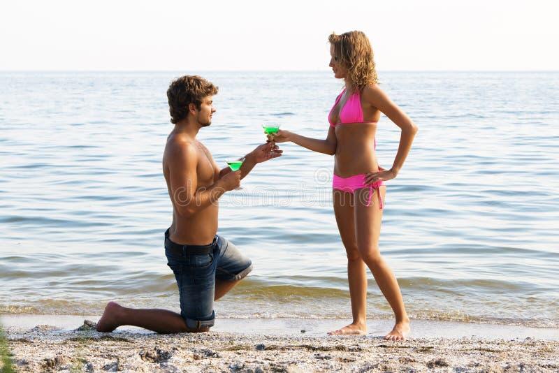 Junge Paare auf der Küste mit Cocktails stockfotos