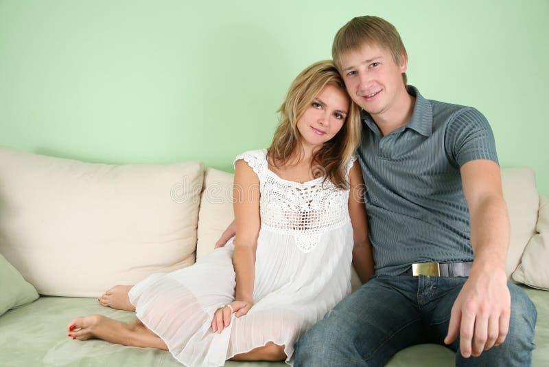 Junge Paare auf Sofa lizenzfreie stockbilder