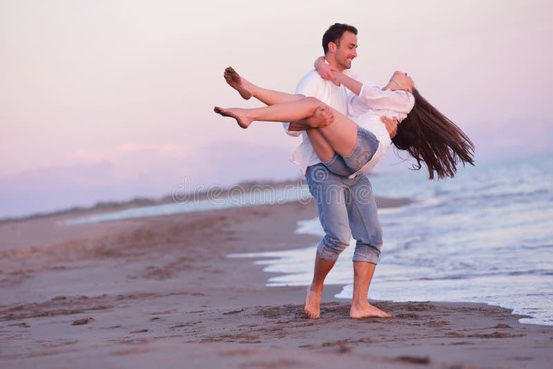 Junge Paare auf Strand haben Spaß lizenzfreies stockfoto