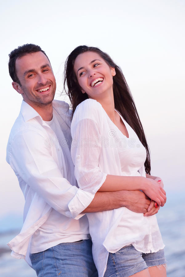 Junge Paare auf Strand haben Spaß stockfoto