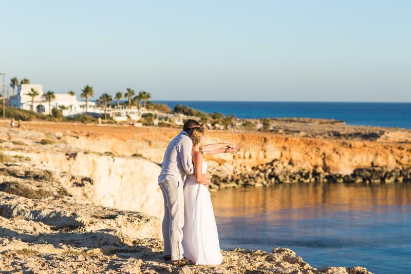 Junge Paare auf Strand-Sommer-Ferien, glücklichem lächelndem Mann und Frauen-gehender Küsten-Seeozean-Urlaubsreise lizenzfreie stockfotografie