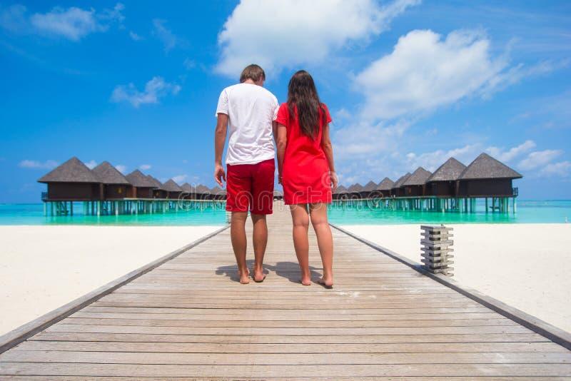 Junge Paare auf tropischer Strandanlegestelle an perfektem lizenzfreie stockfotografie