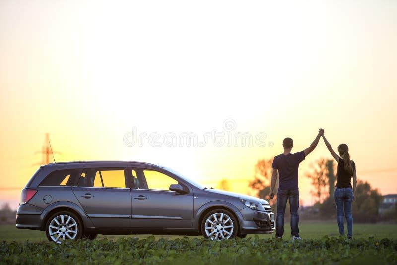 Junge Paare, d?nne attraktive Frau mit langem Pferdeschwanz und athletische Mannholding hoben Arme am silbernen Auto auf dem gr?n stockbilder