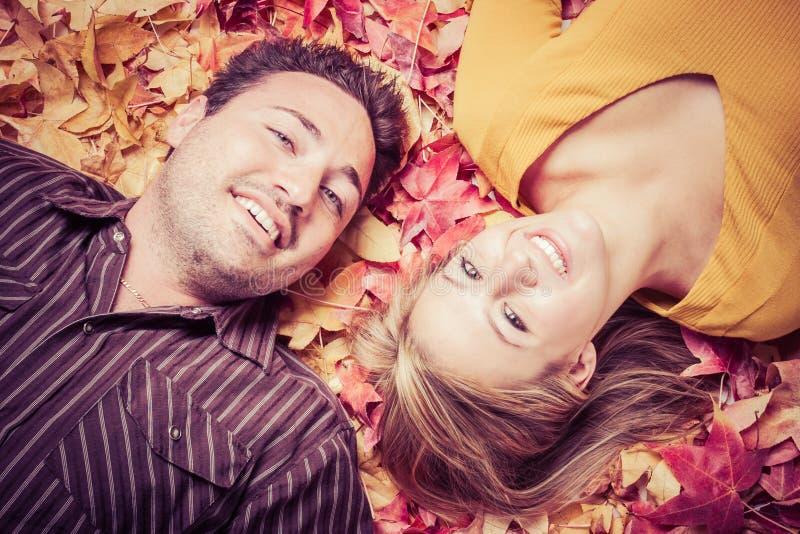 Junge Paare in den Blättern lizenzfreie stockfotografie