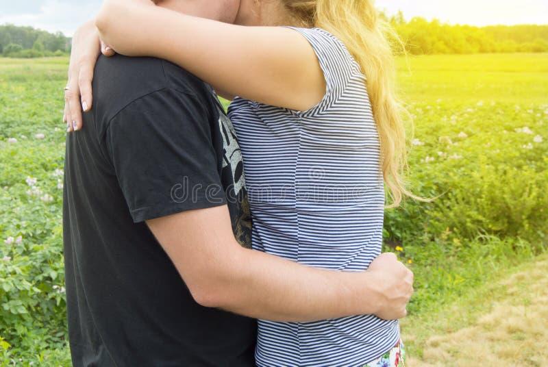 Junge Paare in den Liebesm?nnern und -frauen, die auf Grashintergrund, sonniger Sommertag in der Landschaft in der Natur umarmen lizenzfreies stockbild