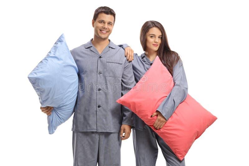 Junge Paare in den Pyjamas, die Kissen halten stockfoto