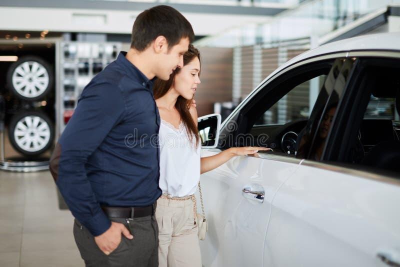 Junge Paare in der eleganten Sommerzeitkleidung wählen einen Neuwagen am Auto-Vertragshändler lizenzfreies stockbild