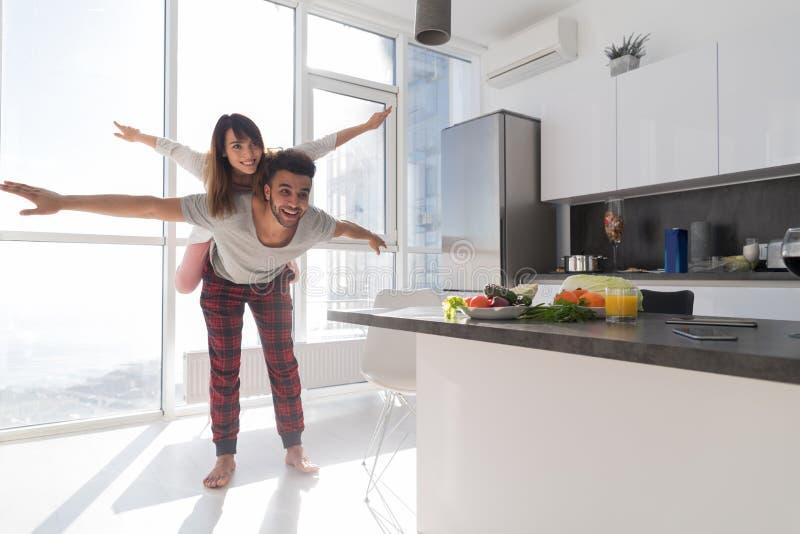 Junge Paare in der Küche, Liebhaber-hispanischer Mann Carry Asian Woman Modern Apartment lizenzfreie stockfotografie
