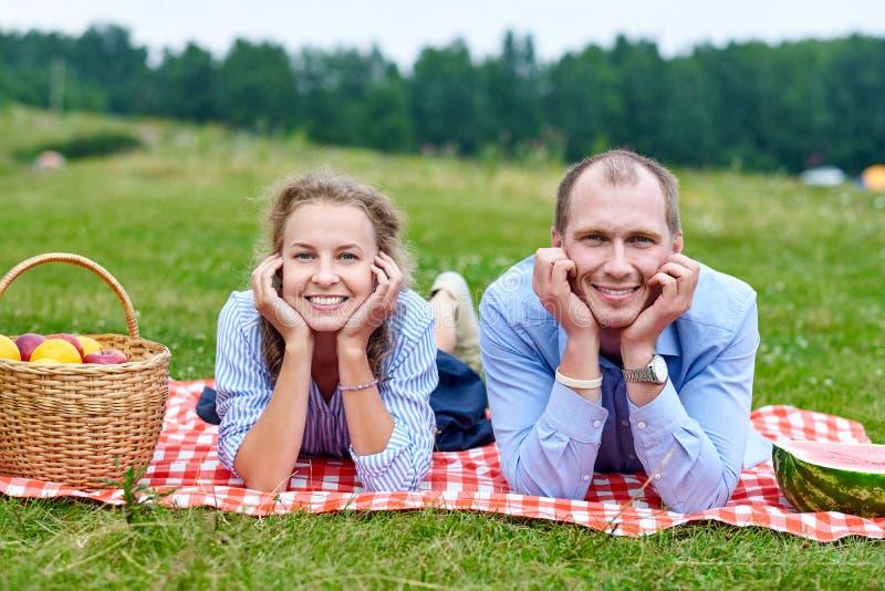 Junge Paare in der Liebe auf dem Picknick, das auf Tischdecke in der roten Zelle liegt Liebespaare, die in der Natur in der Wiese stockfotografie