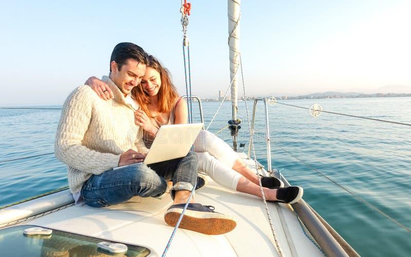 Junge Paare in der Liebe auf dem Segelboot, das Spaßtelearbeit am Laptopglücklichen Luxuslebensstil auf Yachtsegelboot hat stockbild