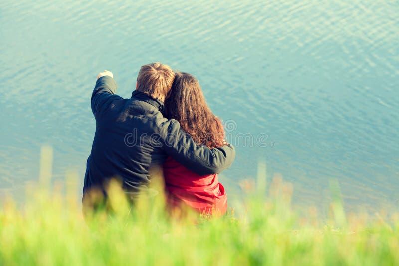 Junge Paare in der Liebe, die auf der Küste sitzt lizenzfreies stockfoto