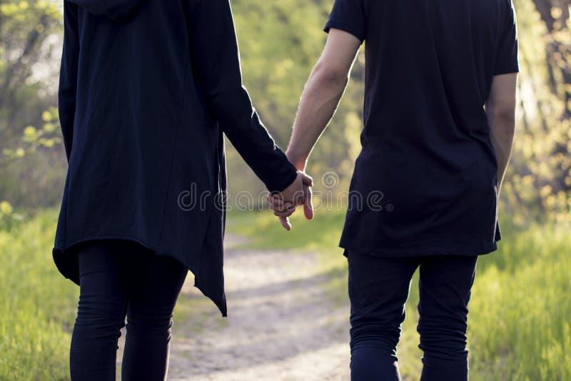 Junge Paare in der Liebe, die in das Sommerparkhändchenhalten geht stockfoto