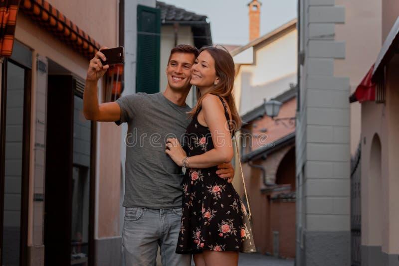 Junge Paare in der Liebe, die ein selfie w?hrend des Einkaufens in einer Gasse im ascona nimmt lizenzfreies stockfoto
