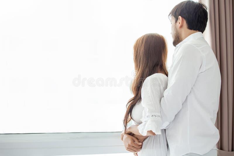Junge Paare in der Liebe, die einander zusammen morgens umfassend auf Fenster im romantischen Moment des Bettraumes nachher aufzu lizenzfreie stockfotos