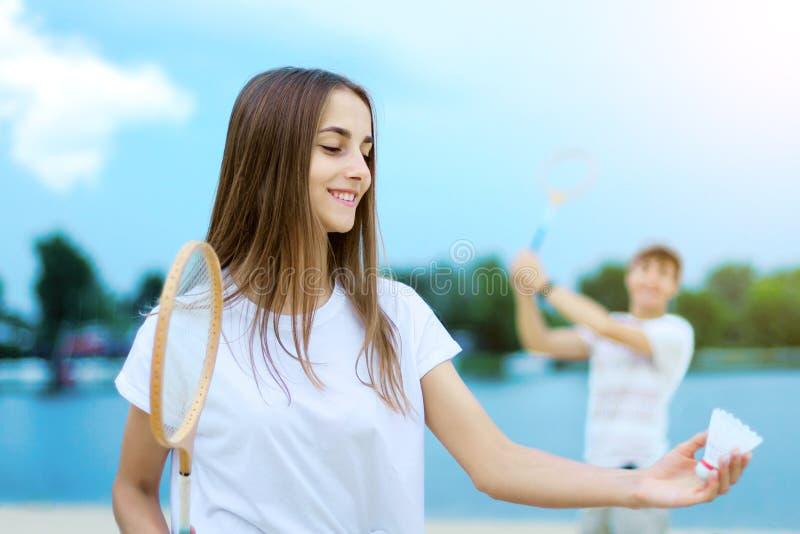 Junge Paare in der Liebe, die im Badminton spielt lizenzfreies stockfoto