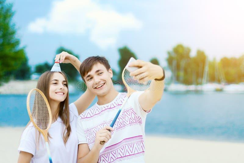Junge Paare in der Liebe, die im Badminton spielt lizenzfreie stockbilder