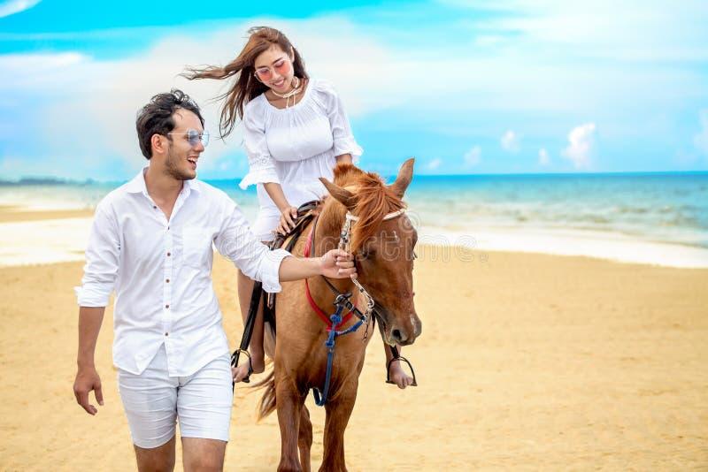 Junge Paare in der Liebe, die mit dem Pferd am Seestrand auf blauem Himmel geht Sommerferien der Flitterwochen tropische See Brau lizenzfreie stockfotografie