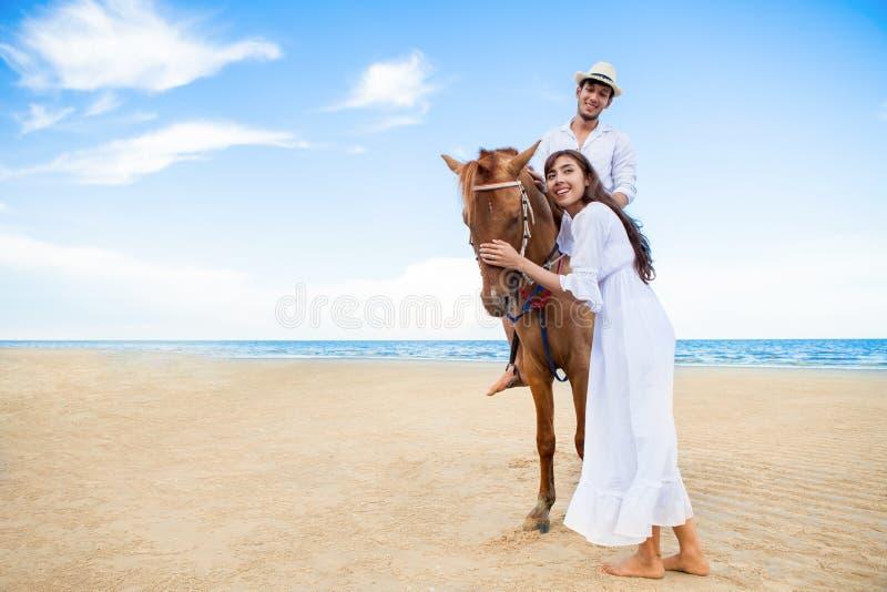Junge Paare in der Liebe, die mit dem Pferd am Seestrand auf blauem Himmel geht Sommerferien der Flitterwochen tropische See Brau lizenzfreie stockfotos
