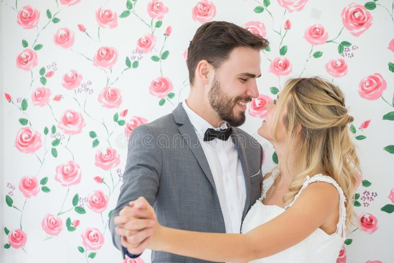 junge Paare in der Liebe Hochzeitsbraut und -bräutigam, die zusammen tanzen und einander auf Rosenhintergrund betrachten jungverm stockbilder