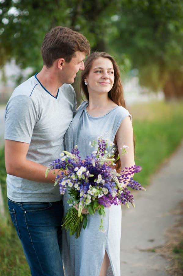 Junge Paare in der Liebe mit einem Blumenstrauß von Blumen auf einem Hintergrund des Weges stockbilder