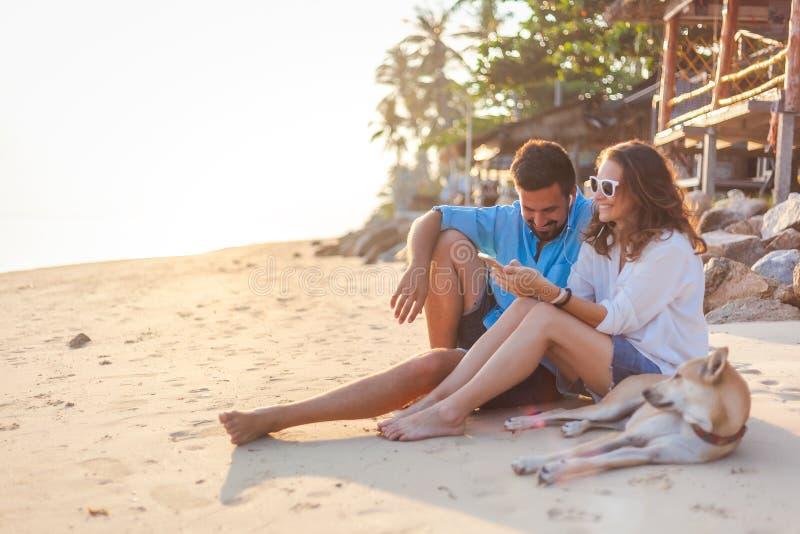 Junge Paare in der Liebe mit einem Hund, der auf der sandigen Küste in den Strahlen des Sonnenuntergangs, Urlaubsreiseflitterwoch stockfotos