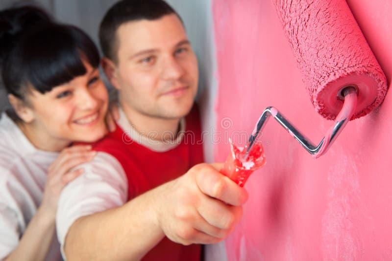 Junge Paare des Arbeitskraftmalens stockbild