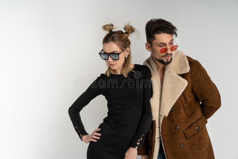 Junge Paare des bärtigen Mannes im Mantel und in der hübschen Frau im schwarzen Kleid mit dem langen blonden Haar lizenzfreies stockbild