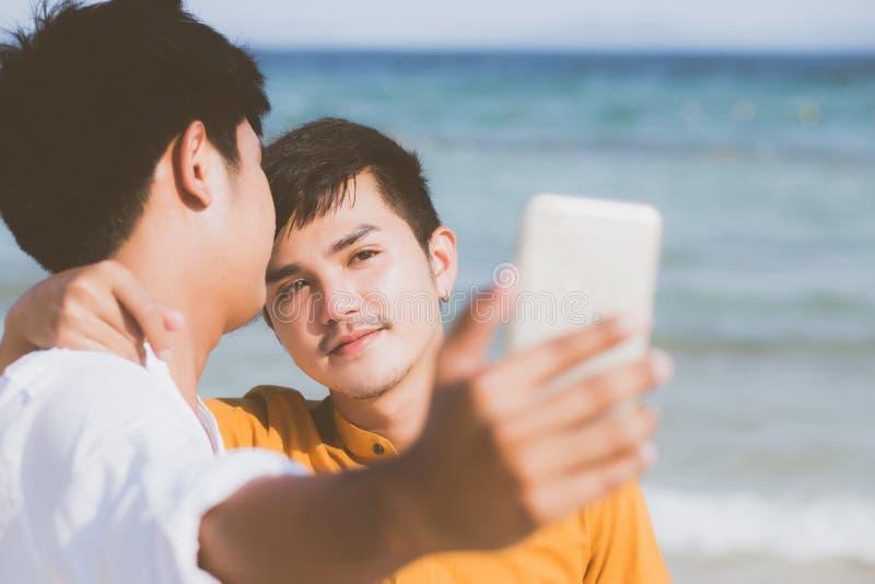 Junge Paare des homosexuellen Porträts, die ein selfie Foto zusammen mit intelligentem Handy machend am Strand lächeln lizenzfreie stockfotos