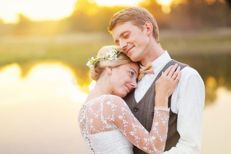 Junge Paare des Jungvermähltens durch See lizenzfreies stockbild