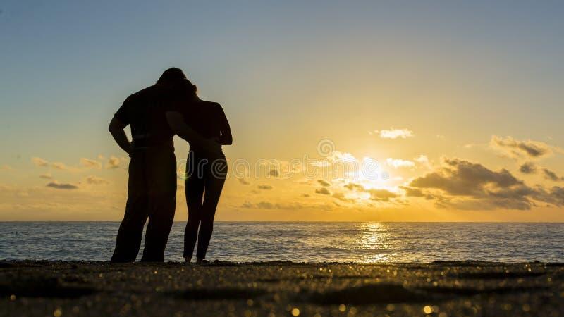 Junge Paare des Liebhaberhändchenhaltens in Richtung zum Meer bei Sonnenuntergang Mann und Frau in der Liebe lizenzfreie stockfotos
