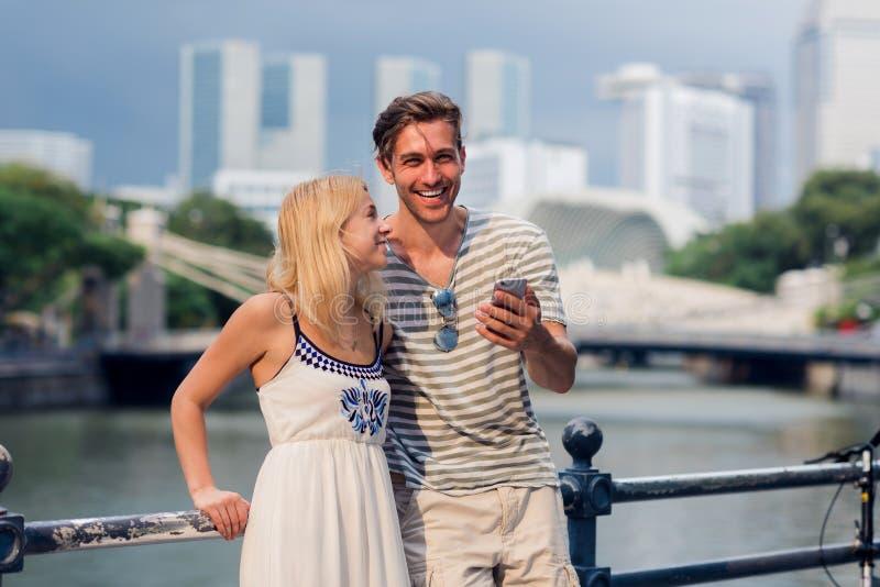 Junge Paare des Touristen, der Handy verwendet lizenzfreie stockfotografie