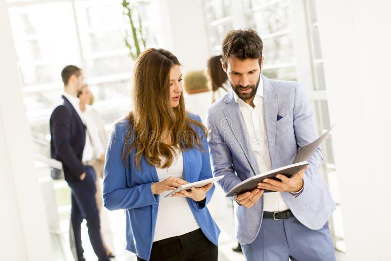 Junge Paare, die über Geschäft sich besprechen lizenzfreie stockfotos
