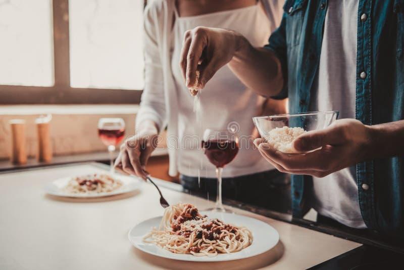 Junge Paare, die Abendessen und Getränk-Rotwein kochen stockbilder