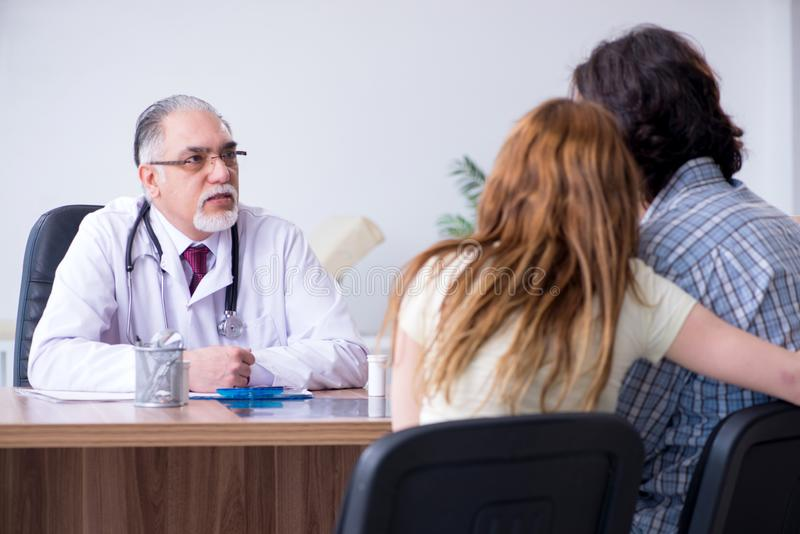 Junge Paare, die alten männlichen Doktor besuchen lizenzfreies stockbild