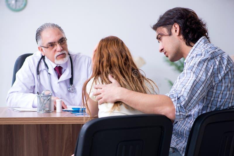 Junge Paare, die alten männlichen Doktor besuchen stockfoto